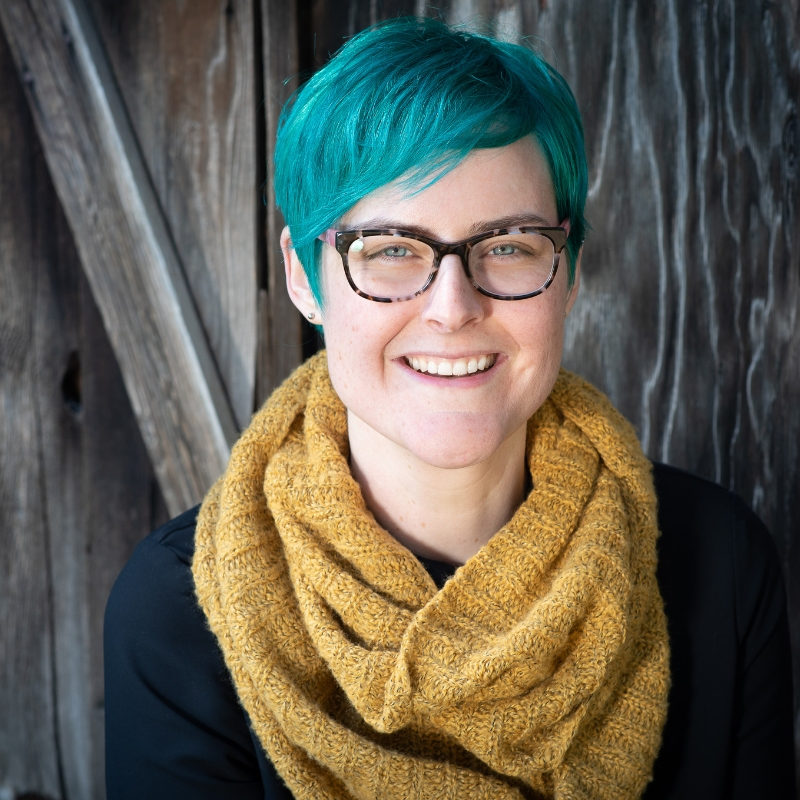 Kate Ristau photo - Woman with blue hair and brown background yellow scarf